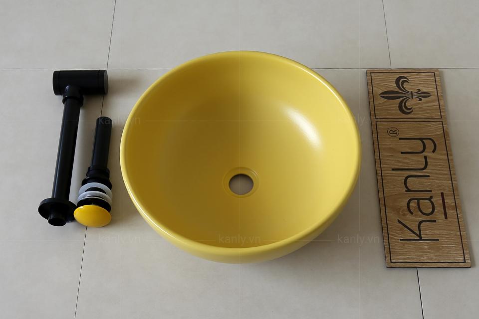 Nút nhấn xả nước màu vàng đồng bộ với màu chậu sứ